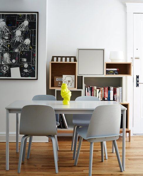 A neon vase by Michael Geertsen contrasts with a gray Base table by Mika Tolvanen and coordinating Nerd and Visu chairs, all for Muuto.