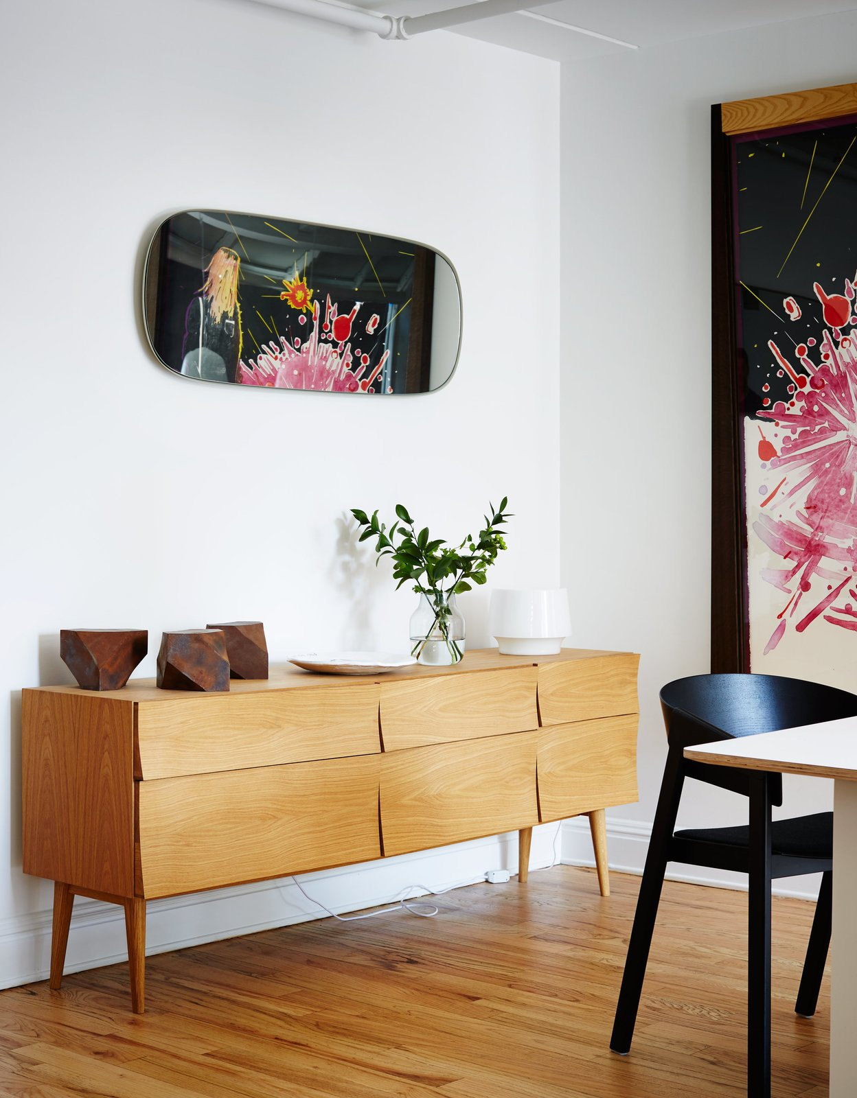 In the opposite communal area, which is separated by the kitchen, a Reflect sideboard by Søren Rose holds a white Cosy lamp by Harri Koskinen and a vase by Andreas Engesvik. Tagged: Dining Room and Storage.  Photo 9 of 12 in A Danish Design Kingpin Moves to NYC with a Shipping Container of Furniture in Tow