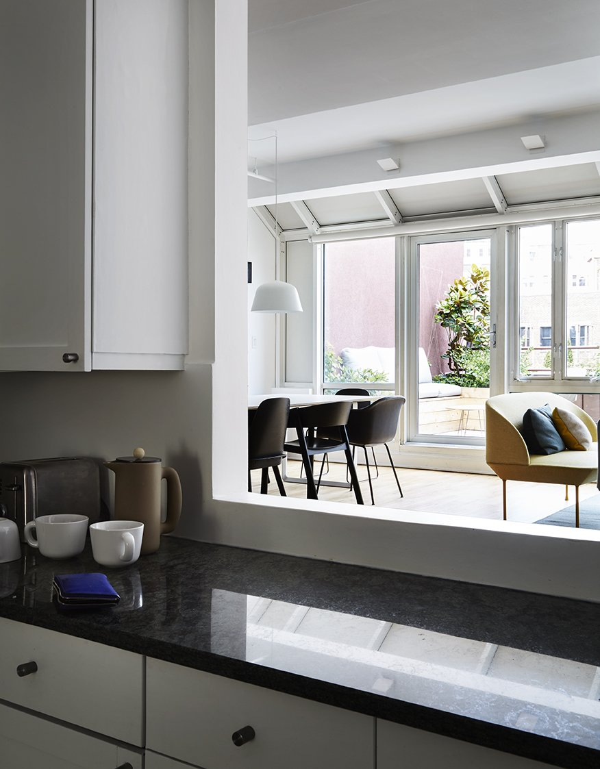 An opening in the kitchen wall allows a view of the terrace from behind the black marble counter. A Danish Design Kingpin Moves to NYC with a Shipping Container of Furniture in Tow - Photo 7 of 12