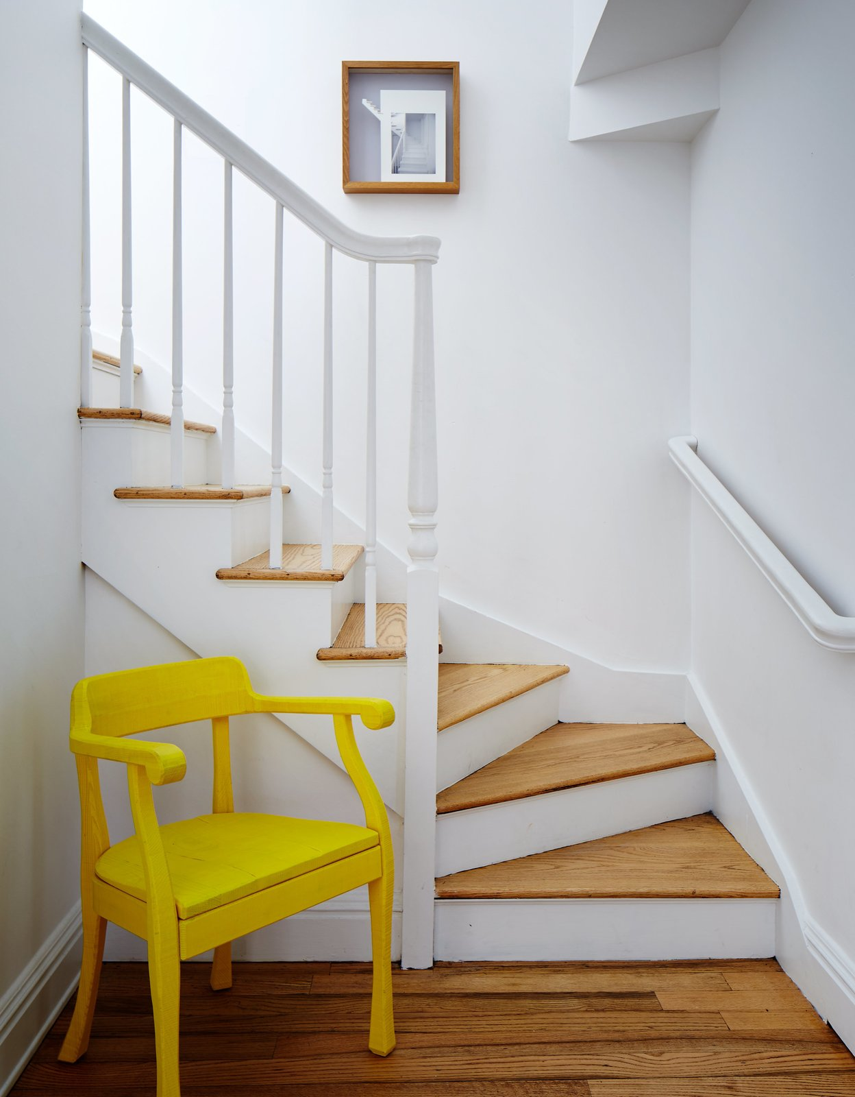In the hallway, a yellow Raw chair by Jens Fager for Muuto pops against the white staircase. Tagged: Staircase, Wood Tread, and Metal Railing.  Photo 13 of 14 in A Danish Design Kingpin Moves to NYC with a Shipping Container of Furniture in Tow