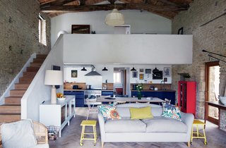 Over a Decade, Two Furniture Designers Reimagine a 300-Year-Old Barn - Photo 2 of 11 - Paired with a lime rendered staircase, a gray Moreau sofa by Pinch and vintage yellow side tables offer bright contrast to the living room's limestone walls and timber frame. The couple laid some 20,000 pieces of reclaimed oak to create the floor's herringbone pattern.