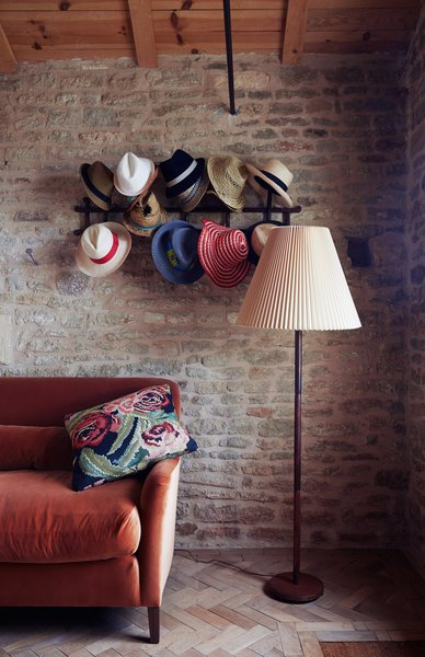 """In a cozy nook the family calls the """"snug,"""" hats hang from a Thonet rack above a Noelle sofa by Pinch, which is upholstered in orange velvet by Kravet."""