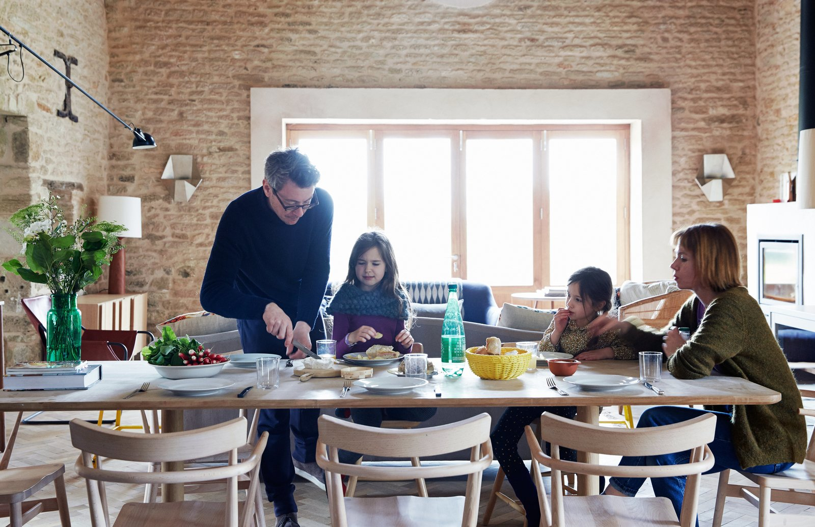 The family gathers at an early prototype of the Achilles table from the Pinch collection. Surrounding it are chairs that were designed by Russell and produced by Ercol for London's Holland Park School. The couple built the doors and windows themselves.