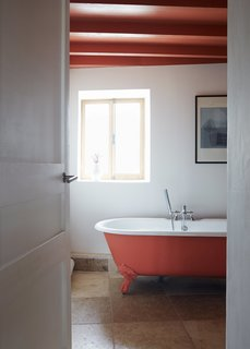 Over a Decade, Two Furniture Designers Reimagine a 300-Year-Old Barn - Photo 9 of 11 - A coat of Orange Aurora paint by Little Greene enlivens an Astonian Rimini clawfoot tub.