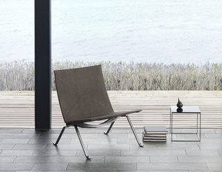 10 Things You Didn't Know About Poul Kjærholm - Photo 5 of 10 - As an evolution from the PK25, the PK22 is less sculptural and more refined. The chair made its first appearance in 1956. Instead of being made from one piece of steel, the construction allows the chair to be broken down, which makes it easier to ship. In considering that every aspect of the design counted, even the screws have aesthetic appeal. For the anniversary, the steel frame is darkened and finished in a nubuck leather.
