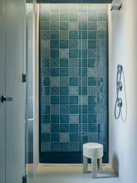 """Tucked in a corner of the master bedroom, a curbless shower with Cea fixtures showcases a wall of patterned Italian tiles that coordinate with those used on the range hood in the kitchen.The designers sought to imbue the apartment's minimalist framework with a handcrafted touch. """"We wanted to add natural and warm elements to the palette,"""" Di Stefano says."""