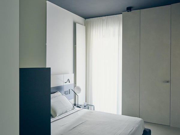 A custom lacquered-wood headboard with built-in task lights by MLE complements a Pianca bed in the master bedroom. An IC Lights T lamp by Michael Anastassiades for Flos offers additional illumination.