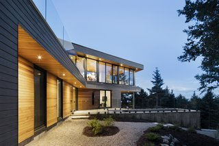 A Home Inspired by the Stars Soars Off the Ground - Photo 1 of 5 - The house is finished in a gray wood facade while the roof or most private areas of the home are covered in western cedar. The cedar extends into the interior for continuity.