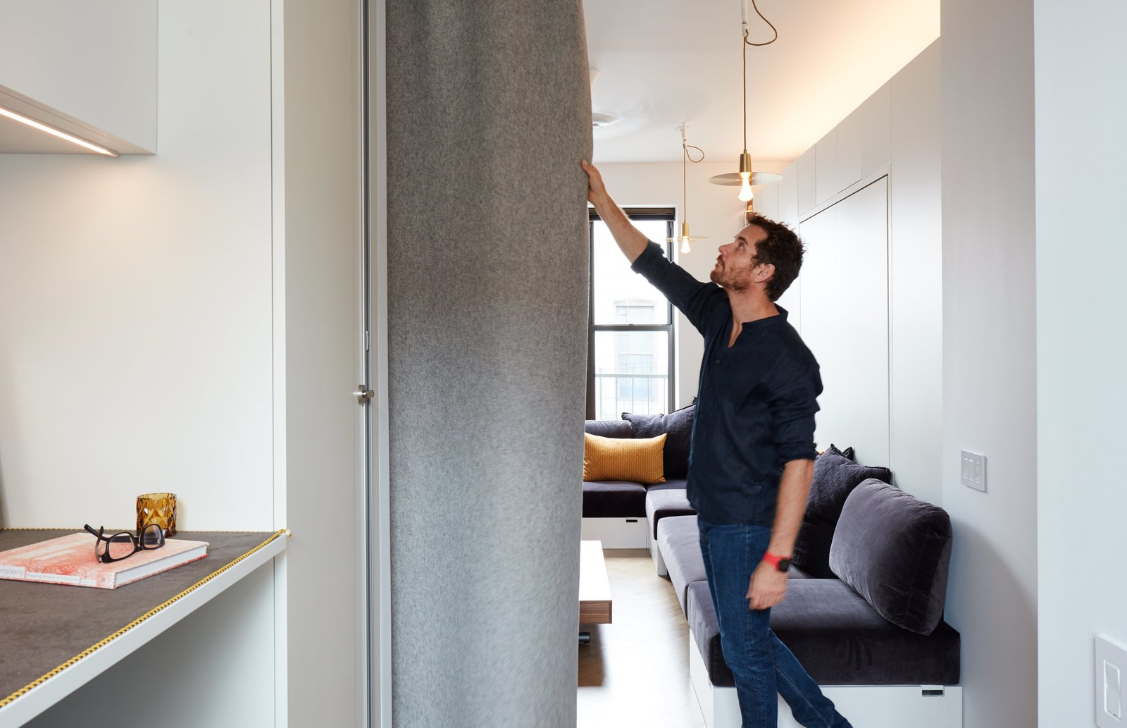 Graham Hill, a sustainability advocate whose TED talks have delved into the benefits of living small, put his own lessons into practice at his 350-square-foot apartment, which he shares with his partner and two dogs. Quick transitions, like drawing the FilzFelt curtain, convert the living space into a bedroom. Tagged: Living Room, Sofa, Sectional, Storage, Bookcase, Shelves, Pendant Lighting, Coffee Tables, Ceiling Lighting, and Light Hardwood Floor.  Photo 2 of 16 in At His 350-Square-Foot Apartment, Small Space Champion Graham Hill Practices What He Preaches