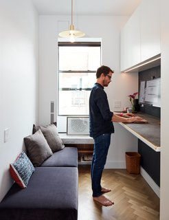 At His 350-Square-Foot Apartment, Small Space Champion Graham Hill Practices What He Preaches - Photo 6 of 15 - Graham, an entrepreneur, works from a fold-down New Table Concept by Resource Furniture. The reusable earthenware mug, a replica of the classic coffee-to-go cups served at New York's Greek diners, is his own design.