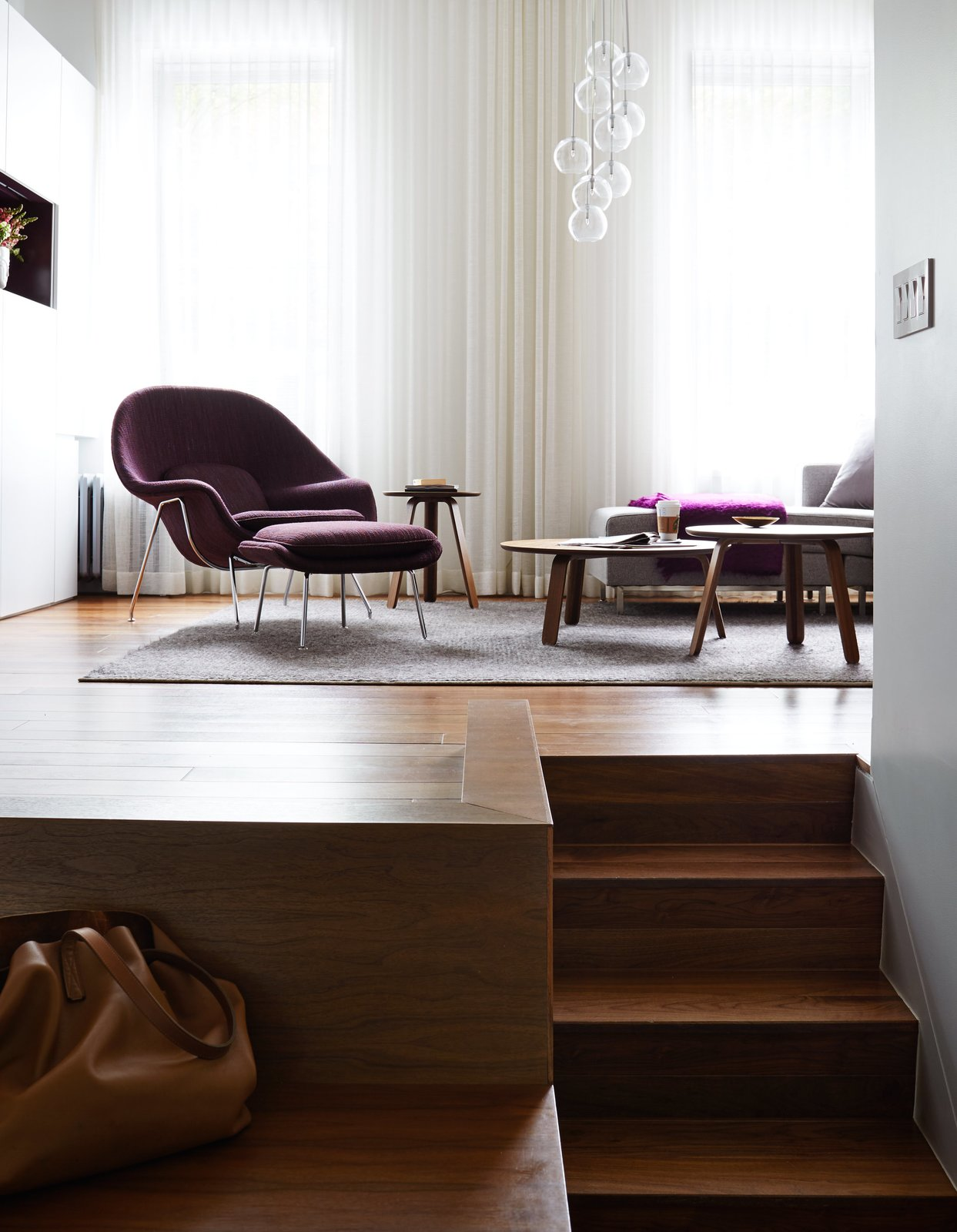 The unusual layout of René Roupinian's Upper West Side home is what initially attracted her to the space, but the three-level plan proved difficult to organize. In his first solo project as STADT Architecture, Christopher Kitterman used a palette of walnut and white to unify the apartment, which he filled with space-saving solutions. Near the entrance, a Goliath table from Resource Furniture can expand to seat up to 10. Tagged: Living Room, Chair, Medium Hardwood Floor, and Coffee Tables.  Photo 5 of 5 in Small Space, Big Design