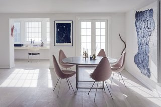 A Recent Trip Leaves Us Dwelling on Denmark - Photo 6 of 14 - The first floor of the home features an open plan that combines the kitchen, dining room, and a small study. Drop chairs by Arne Jacobsen surround a PK58 table by Poul Kjærholm. The study includes the designer's three-legged PK11 chair alongside sculptures by artists and the couple's children.