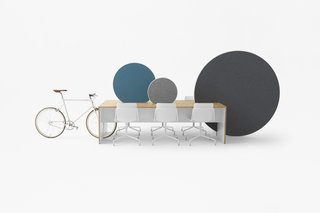 The slots made in the table accommodate a bicycle for commuters and various whiteboards to divide up space in the office.