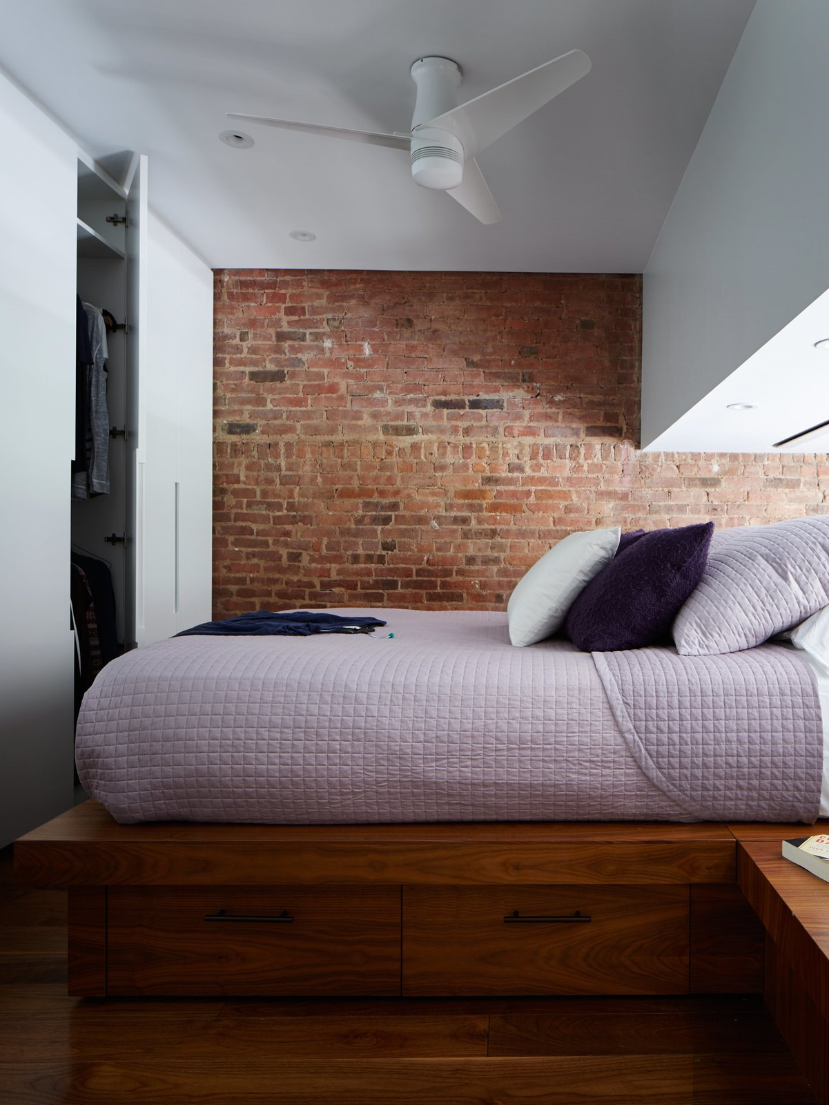 A variation on the system serves as a wardrobe in the sleeping loft. Additional storage can be found in the walnut platform with side tables. Although it appears less in the photo, the space between the platform and the lowest part of the ceiling is about four and a half feet, allowing René to comfortably sit up in bed. A Lutron screen lowers for privacy. Tagged: Bedroom, Bed, Recessed Lighting, Medium Hardwood Floor, Ceiling Lighting, Night Stands, and Storage.  Photo 4 of 9 in A 16-Foot-Wide Triplex Is Cleverly Reconfigured to Feel Extra Spacious