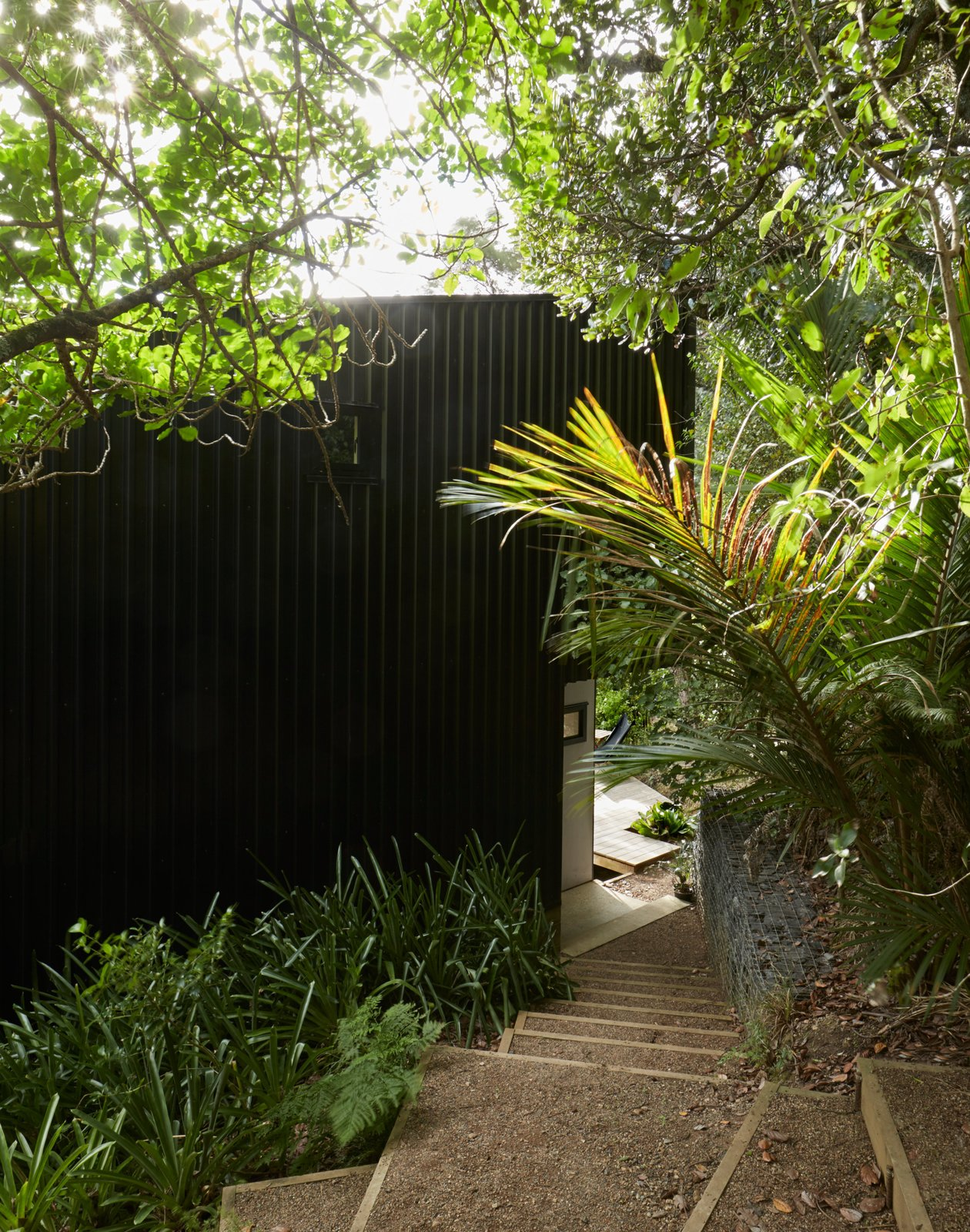 """Seeking a private escape from busy Auckland life, Milton Henry and Mark Summerville purchased an """"unbuildable"""" lot on Waiheke Island and then rehabbed it over 15 years.A clearing in the bush dictated the footprint,resulting in two stacked volumes that form a tower-like structure over four split levels. It took a customized trailer to bring materials to the steep site.  Photo 2 of 13 in A Tiny Footprint Isn't So Bad When You Live in a Tower"""