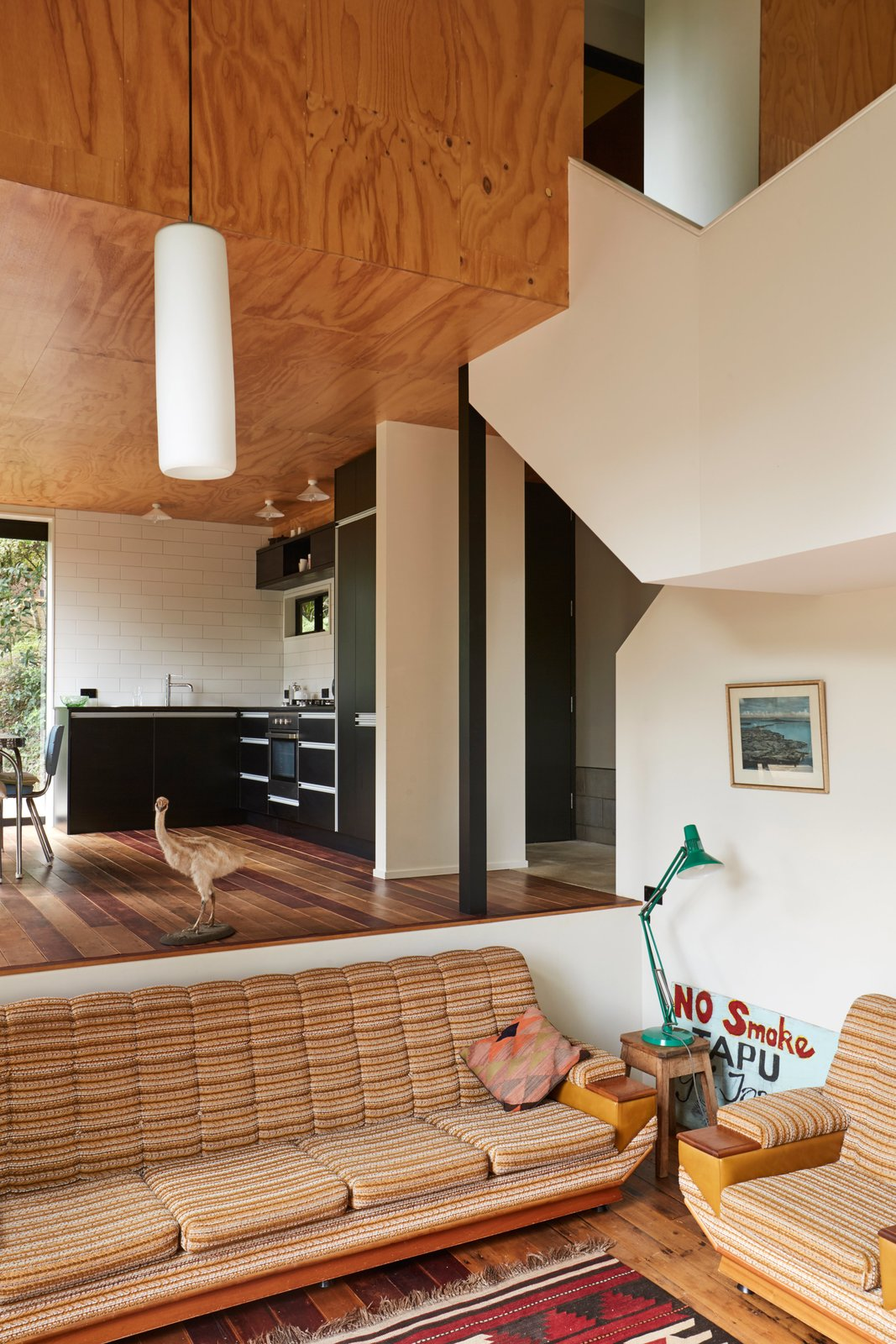 The mezzanine daybed is set in a windowed nook within shelves recycled from a Lundia system. Peta Tearle designed the color scheme and chose the black Melteca kitchen cupboards, which echo the exterior. Tagged: Kitchen.  Photo 11 of 13 in A Tiny Footprint Isn't So Bad When You Live in a Tower