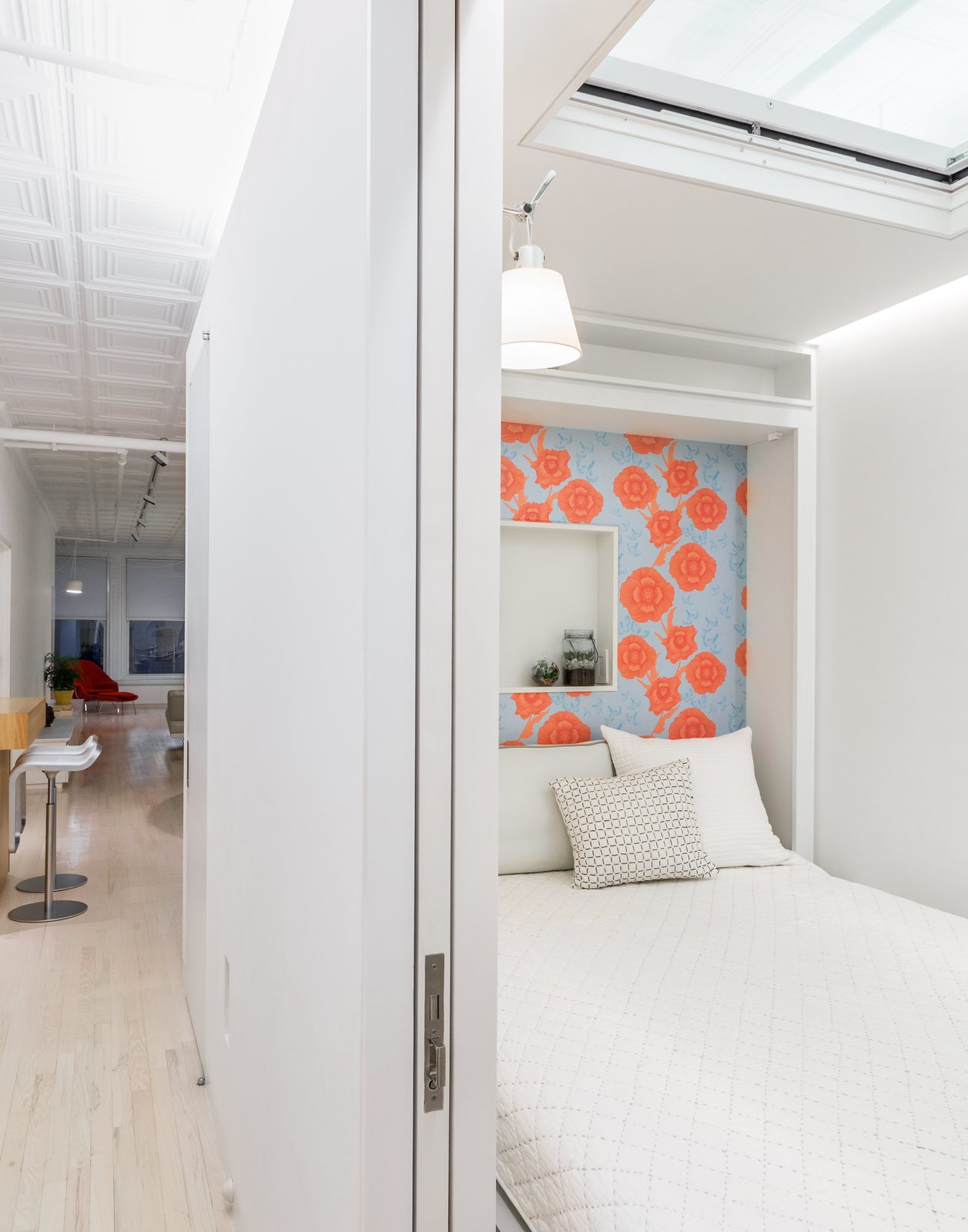 """Across from it, a Murphy bed by Resource Furniture—lined with Camilla Meijer wallpaper and featuring a customized niche—allows the space to function as a guest room. An electric Velux skylight frames views of the original tin plates above. The architects chose to leave space between the top of the structure and the ceiling to maintain the rectangular proportions of the loft. """"It reads right away,"""" Singer says of the volume. """"It's very satisfying."""""""