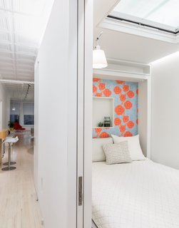 "This 60-Square-Foot Structure Divides and Conquers in a Manhattan Renovation - Photo 7 of 8 - Across from it, a Murphy bed by Resource Furniture—lined with Camilla Meijer wallpaper and featuring a customized niche—allows the space to function as a guest room. An electric Velux skylight frames views of the original tin plates above. The architects chose to leave space between the top of the structure and the ceiling to maintain the rectangular proportions of the loft. ""It reads right away,"" Singer says of the volume. ""It's very satisfying."""