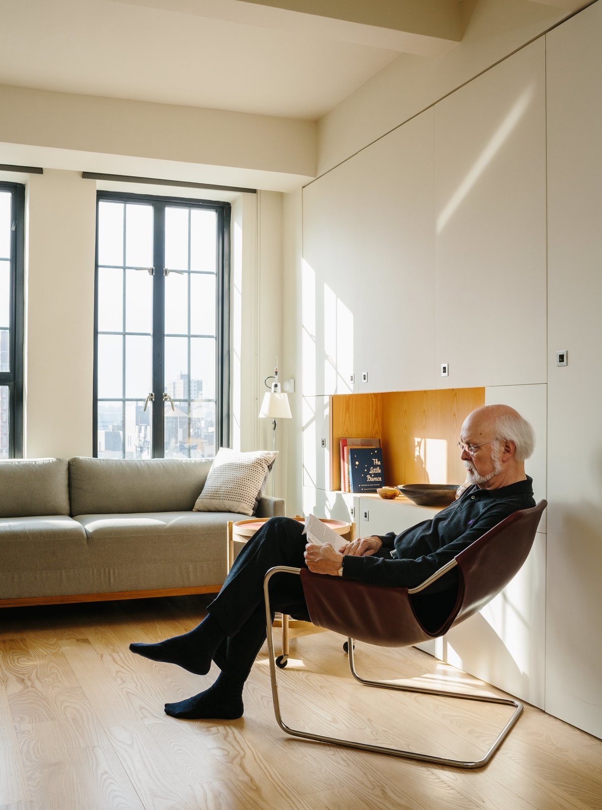 Resident Paul Andersson lounges in a Paulistano armchair by Paulo Mendes da Rocha. Tagged: Living Room, Chair, Sofa, End Tables, Storage, Coffee Tables, Shelves, Lamps, Table Lighting, and Light Hardwood Floor.  Photo 4 of 9 in A Pivoting Wall Makes This Tiny Studio a Fit For Any Occasion