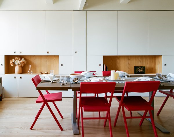 The red Piana folding chairs are by David Chipperfield for Alessi; Garneau custom-designed the millwork tabletop and stainless-steel legs. Tagged: Dining Room, Chair, Table, Storage, Shelves, and Light Hardwood Floor.  Photo 6 of 9 in A Pivoting Wall Makes This Tiny Studio a Fit For Any Occasion