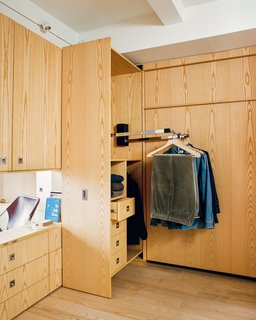 A Pivoting Wall Makes This Tiny Studio a Fit For Any Occasion - Photo 4 of 8 - Stowing the queen-size Room Makers Murphy bed by SICO frees up access to custom built-in cabinets and pull-down closet rods by Hafele that illuminate when the door is opened.