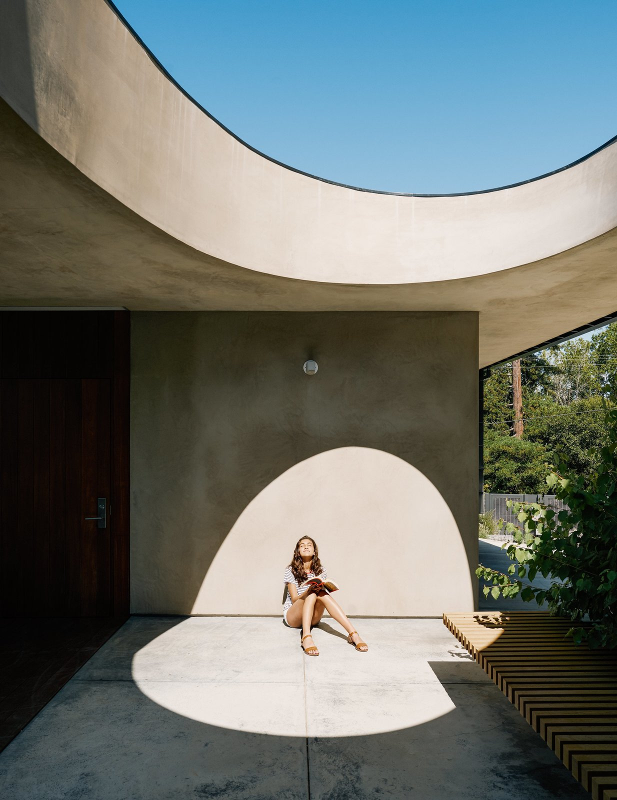 For the breezeway, Schwartz used concrete to achieve the feel of a hardscape courtyard. Uma basks beneath the egg-shaped opening.
