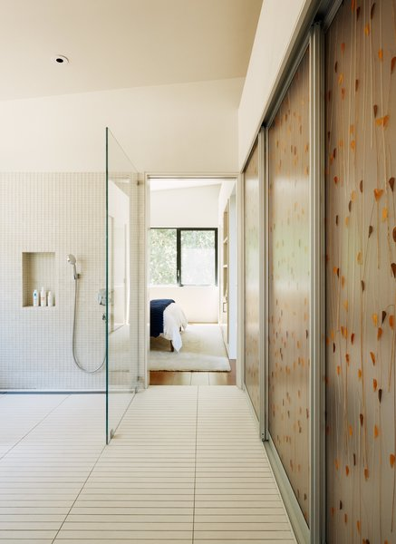 In the bathroom, narrow porcelain floor tiles, which require more grout, provide extra traction to prevent slips. Schwartz chose Hansgrohe's PuraVida shower mixer for its easy grip. Inlaid with a leaf pattern, lightweight and impact-resistant Varia Ecoresin sliding panels by 3form access the washer and dryer.