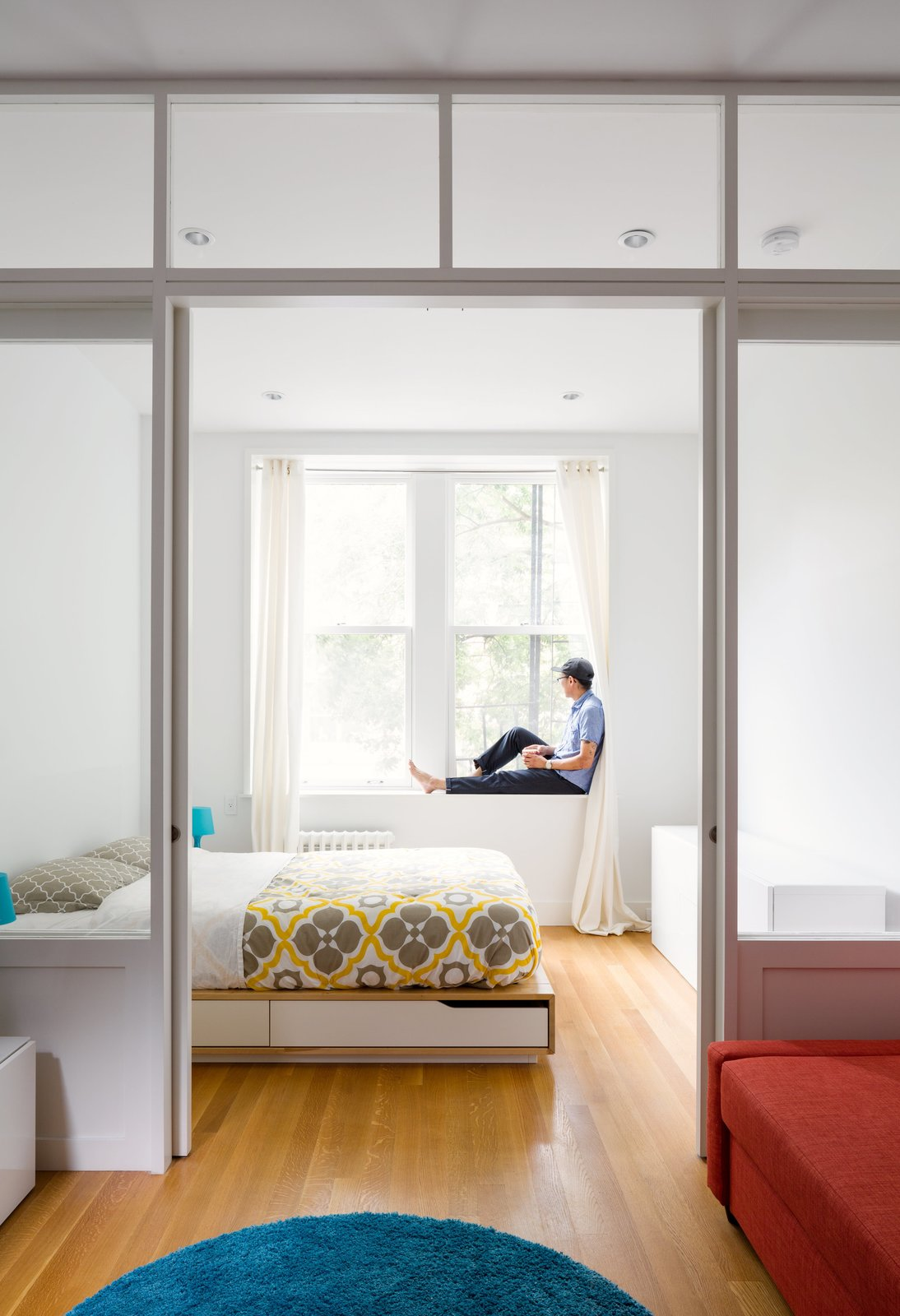 By replacing a wall with a custom wood-and-glass partition, architect Matt Krajewski transformed a previously dark one-bedroom railroad apartment in Manhattan into a light-filled home. Compact furnishings, like a Mandal bed frame from IKEA with integrated storage, maximize every inch of the 390-square-foot unit, housed in a former tenement building. Tagged: Bedroom, Bed, Recessed Lighting, and Medium Hardwood Floor.  Photo 1 of 11 in Cozy and Compact: 10 Tiny Homes in the Big Apple from This 390-Square-Foot Renovation Is Compact Yet Comfortable in Greenwich Village
