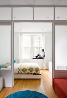 This 390-Square-Foot Renovation Is Compact Yet Comfortable in Greenwich Village - Photo 1 of 9 - By replacing a wall with a custom wood-and-glass partition, architect Matt Krajewski transformed a previously dark one-bedroom railroad apartment in Manhattan into a light-filled home. Compact furnishings, like a Mandal bed frame from IKEA with integrated storage, maximize every inch of the 390-square-foot unit, housed in a former tenement building.