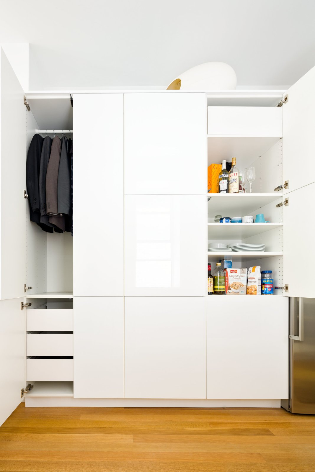 In the kitchen, a single Sektion wardrobe from IKEA is used to stow both clothing and various food and dining items. Throughout the apartment, Krajewski replaced the time-worn flooring, installing new white oak planks by Hull Forest with a buffed oil finish by Waterlox.