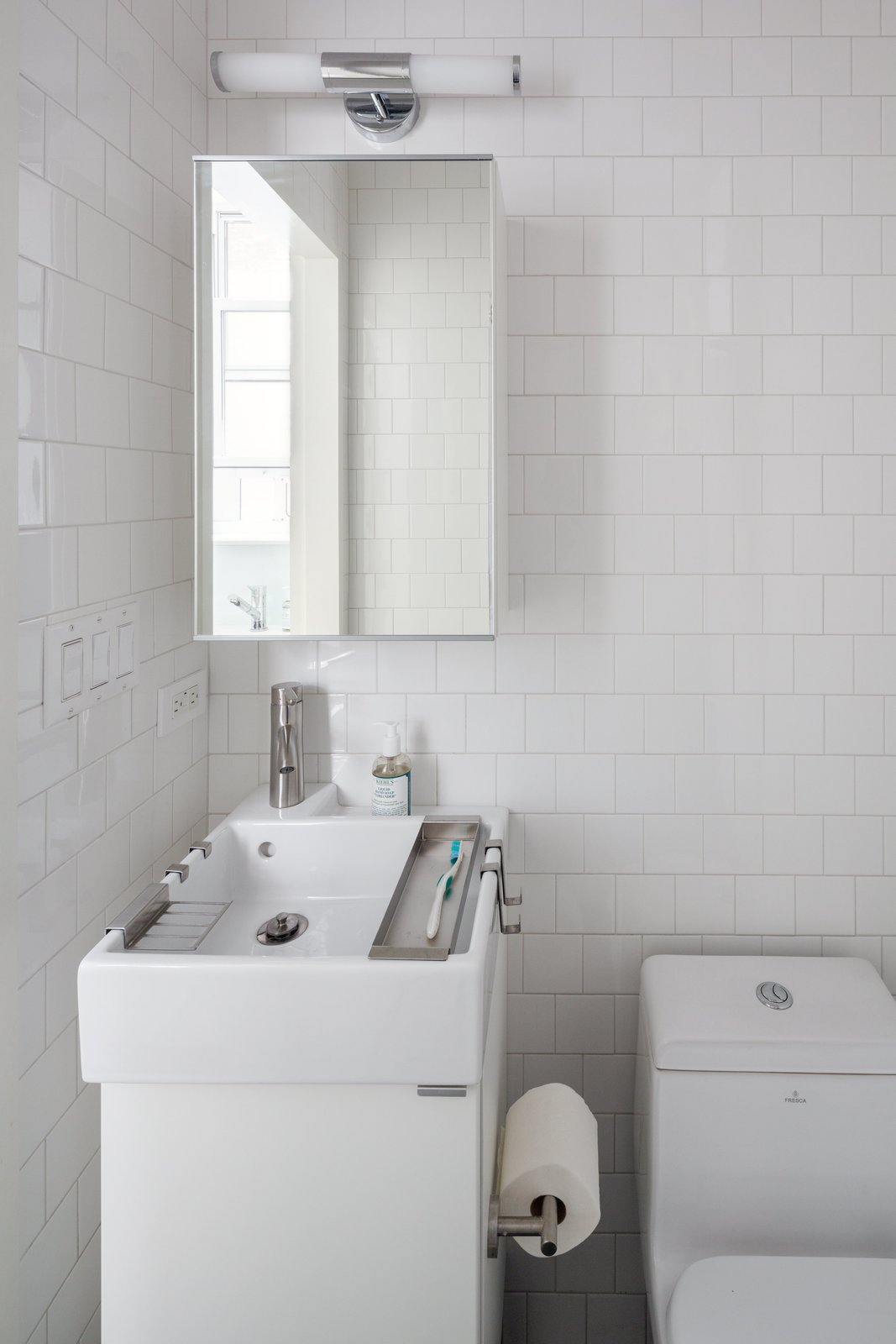 In the bathroom, a compact Lillången sink from IKEA offers a narrow profile for the tight space, yet is deep enough to accommodate hanging storage trays for toiletrie. The toilet is by Fresca and the subway tile is from Mosa.  Photo 9 of 10 in This 390-Square-Foot Renovation Is Compact Yet Comfortable in Greenwich Village