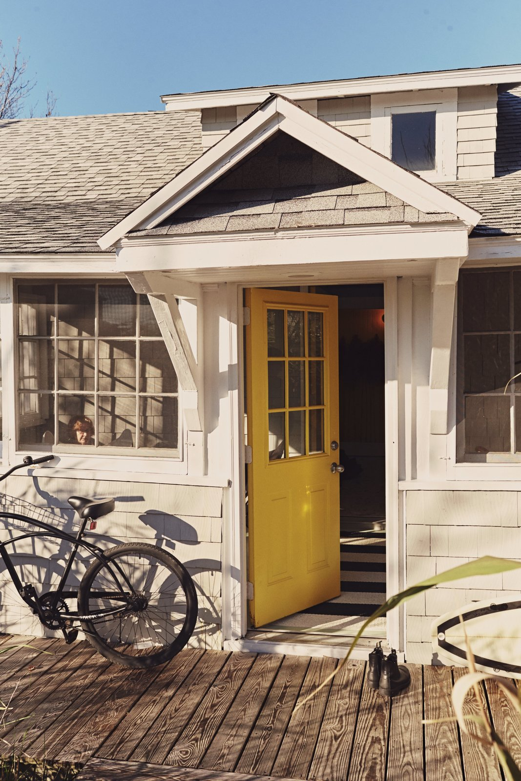 The door to the front porch, painted in Bright Yellow by Benjamin Moore, is inspired by the island's local flora.   Photo 21 of 25 in 25 Bold Ways to Decorate with Yellow