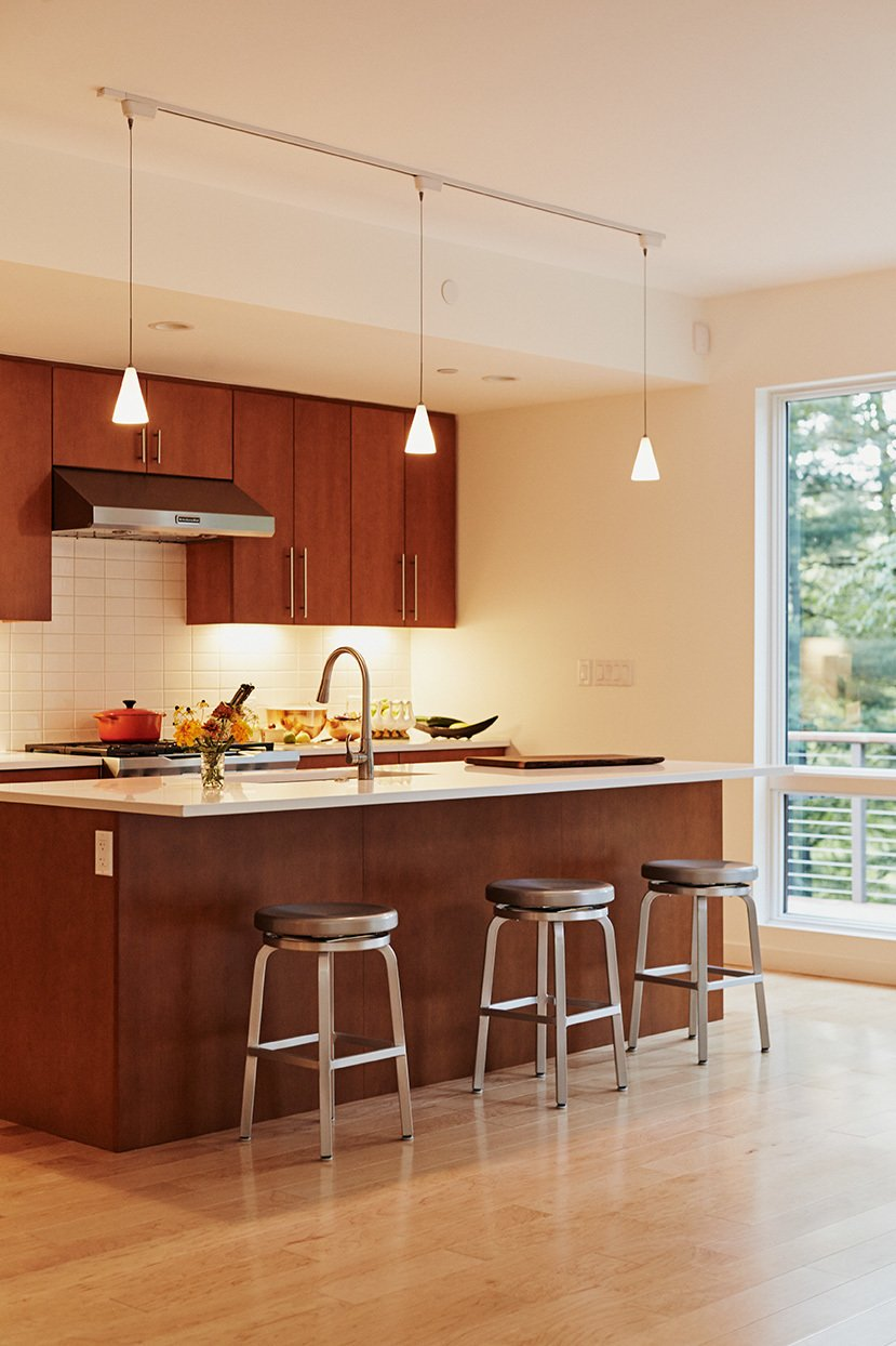 Presented with three possible kitchen units by Blu Homes, the residents selected one that has less cabinetry and a more fluid layout. The bar stools are from Crate and Barrel.  Photo 3 of 9 in Park Place