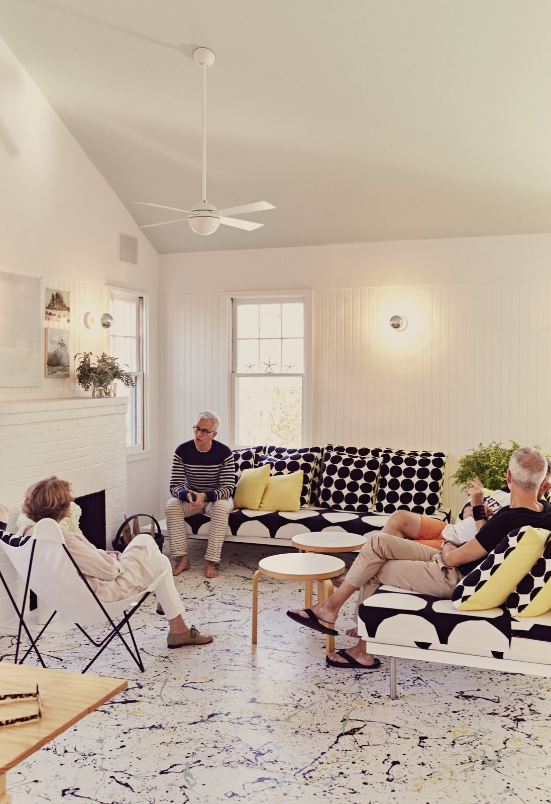 Residents Ann and Tony Spagnola sit with their architects, Peter Stamberg and Paul Aferiat, in front of the whitewashed brick fireplace in the living room. A vintage Butterfly chair joins custom sofas designed by the architects. Coffee tables by Alvar Aalto for Artek and pillows by Marimekko create a clean, Finnish-inflected environment. Tagged: Living Room, Chair, Coffee Tables, End Tables, Sofa, Table, and Wall Lighting.  Photo 2 of 5 in Damaged by Superstorm Sandy, a Fire Island Cottage is Rebuilt