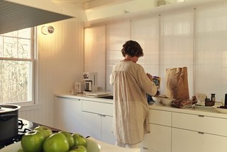 Damaged by Superstorm Sandy, a Fire Island Cottage is Rebuilt - Photo 1 of 6 - .In the galley-style kitchen, Ann sorts groceries into Akurum cabinets from IKEA. For the sconces, the architects selected generic porcelain sockets, then stylized them with silver-cap bulbs.