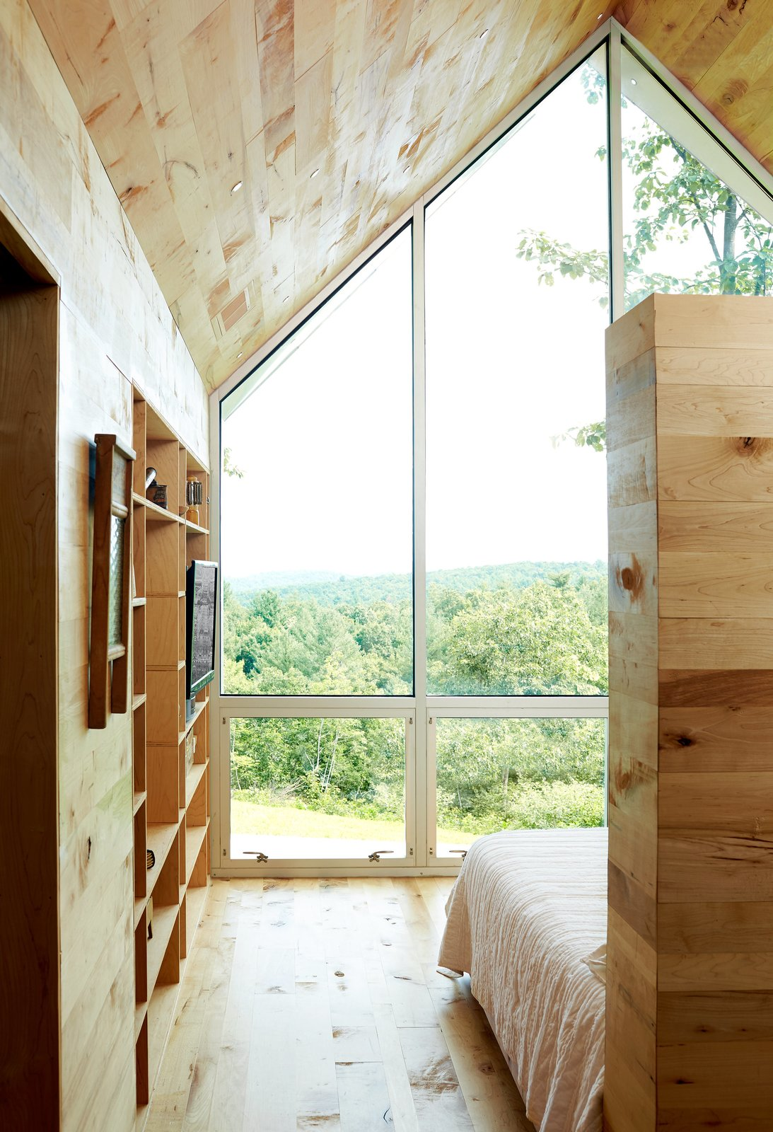 An 800-square-foot addition expands the Virginia home of Lauren and Josh Stegall. Built for $120,000, the structure has a large window overlooking the Blue Ridge Parkway and Sugarloaf Mountain. Tagged: Bedroom, Bed, Storage, Bookcase, and Medium Hardwood Floor. Happy Trails - Photo 2 of 8