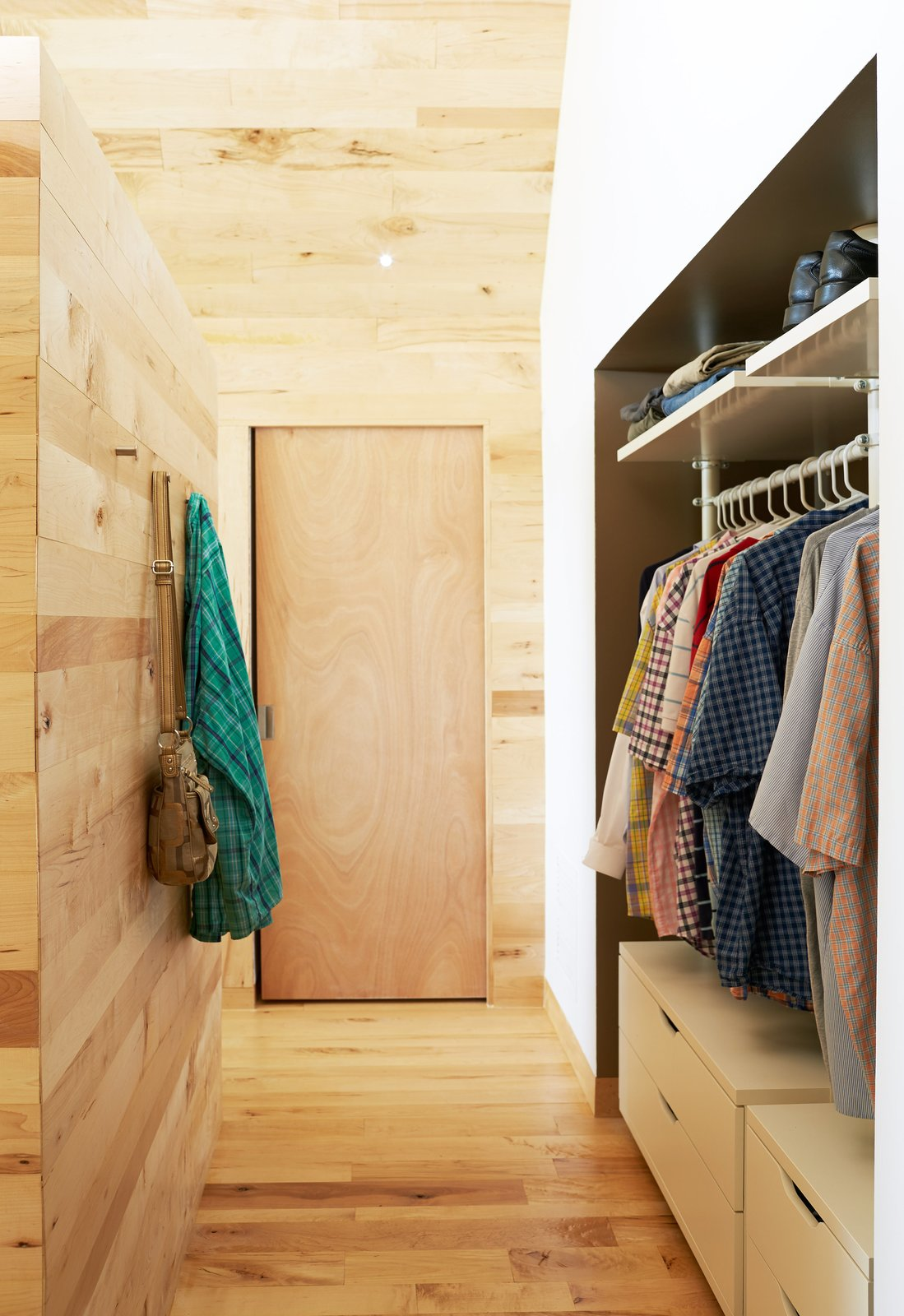 IKEA's Stolmen system holds the couple's clothes in the master bedroom. Solid core maple doors from Lowe's match the structure's interiors, which are lined in wood largely sourced from Union Church Millworks.