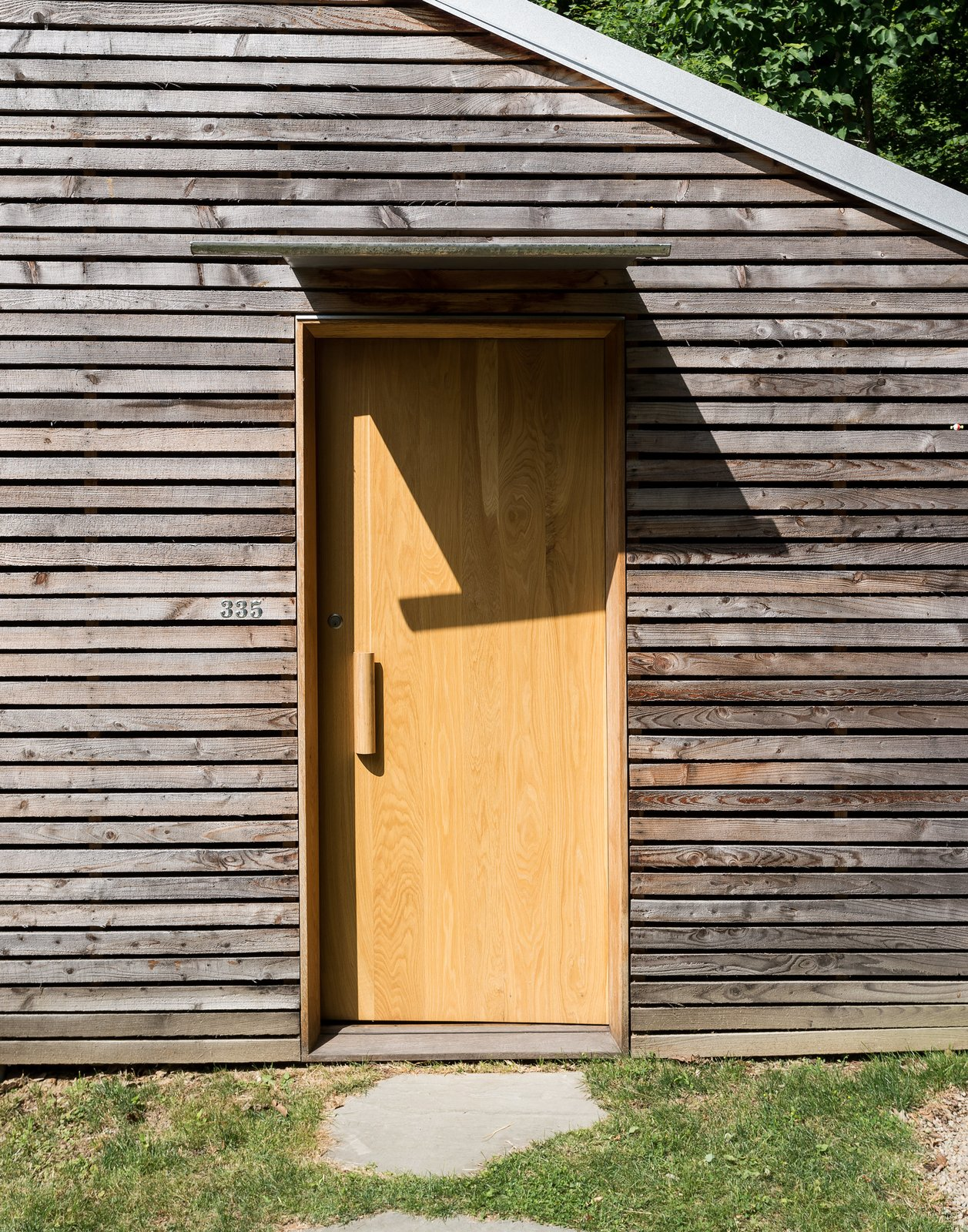 Taking a cue from a nearby farm structure, the couple used thin strips of larch to disguise imperfections in the original concrete block structure.