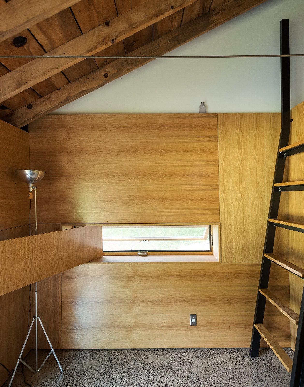 A custom ladder made of bent steel with oak treads leads to the sleeping loft, while a white oak panel swings opens to reveal an inset window. Longtime collaborator Jeffrey Kramer crafted the home's wood elements.