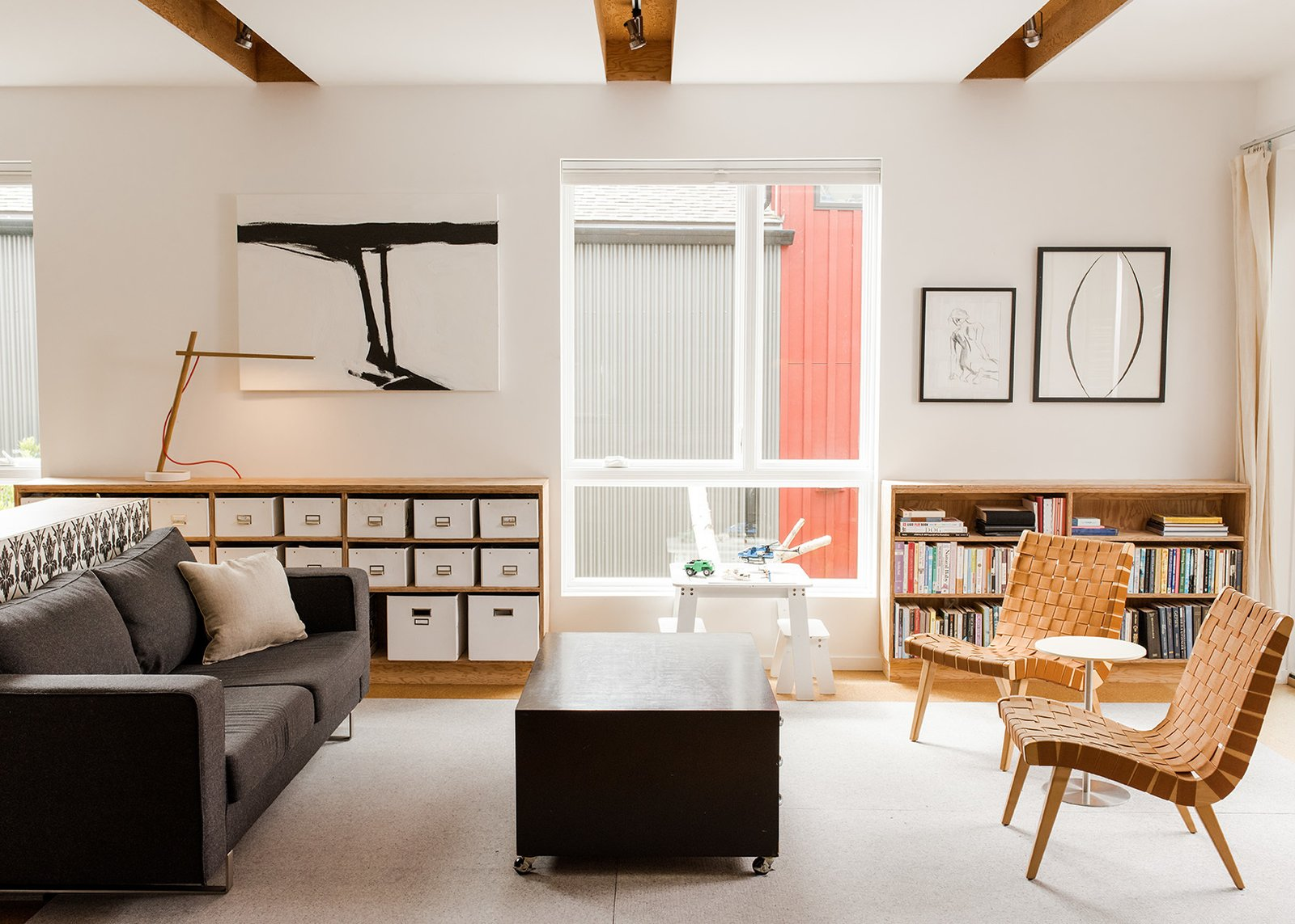 The Davises' living room is filled with modern designs, including two lounge chairs by Jens Risom for Knoll and a BoConcept sofa. Mary Jo created the artwork.  Photo 5 of 15 in It Takes a Village