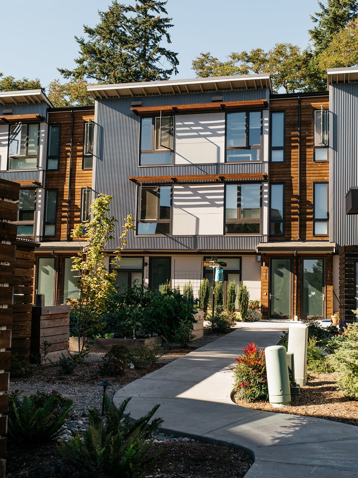 Phase one consists of 23 houses and two apartment buildings with 10 units each. The next two phases, The Grove and The Park, will offer a mix of town houses and condominium apartments. Some critics see these more conventional schemes as diluted versions of the original concept.  Photo 9 of 15 in It Takes a Village