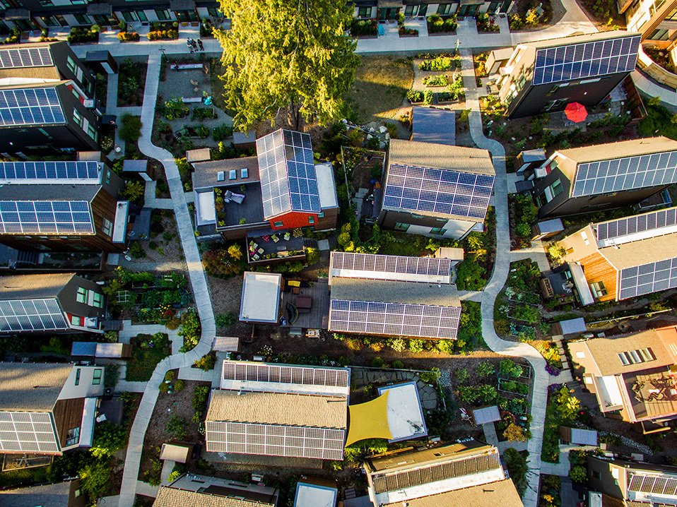 Rooftop Itek solar panels power the community—and are eligible for increased production incentives because they're made locally. Although the panels were optional, every Village resident chose  to install them. Tagged: Exterior, House, and Green Roof Material.  Photo 10 of 15 in It Takes a Village
