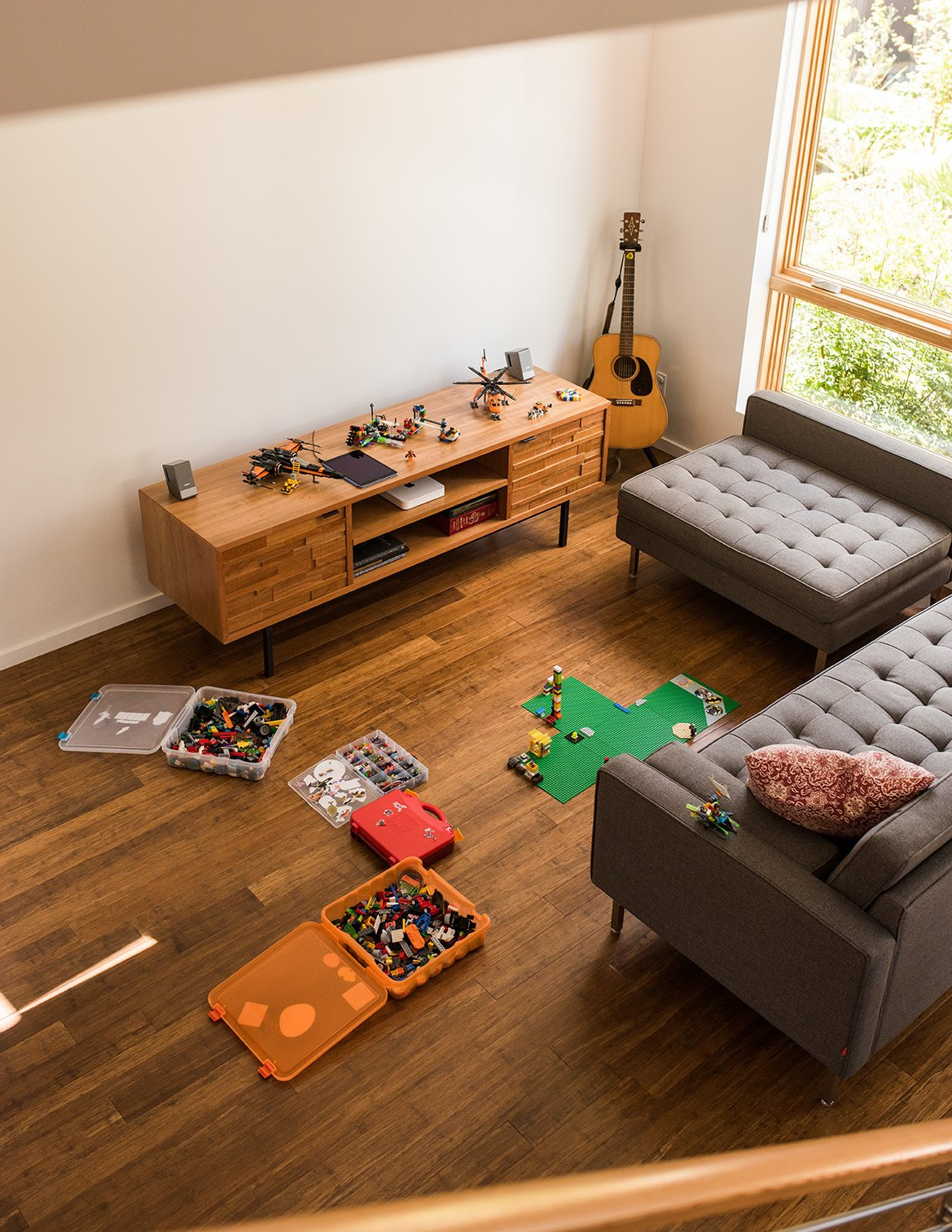 """Chris and Wendy Kozina live with their son, Ben, in a """"Tallis"""" style town house. They selected bamboo floors for the 1,155-square-foot, two-bedroom interior. The family strives to cap their possessions at 500 items—Legos not included. In the living room, an Innes media cabinet from Room & Board is paired with a Gus Modern sectional.  Photo 12 of 15 in It Takes a Village"""