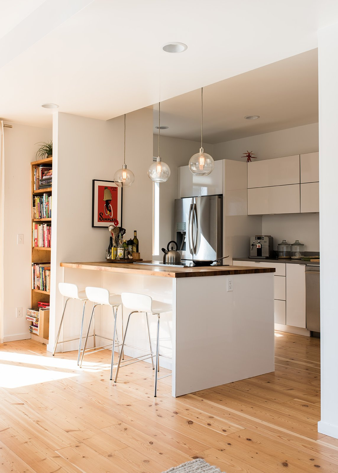 "Marja Preston's family lives in one of Grow's ""Everett"" houses, with three bedrooms in 1,846 square feet. In their kitchen, West Elm pendants hang over a counter of myrtle butcher block sourced from Green Home Solutions. Tagged: Kitchen, Refrigerator, Range, Wood Counter, Light Hardwood Floor, White Cabinet, Ceiling Lighting, Recessed Lighting, and Pendant Lighting.  Photo 14 of 15 in It Takes a Village"