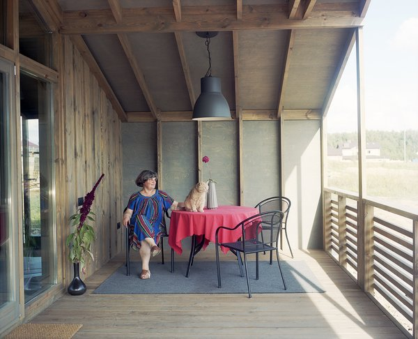 Anna's house is a version of the DublDom 2.87, which has a starting price of 2.87 million rubles (about $46,000). The structure features a porch at each end lined in stained plywood. Anna surveys the countryside from under the gabled roof.