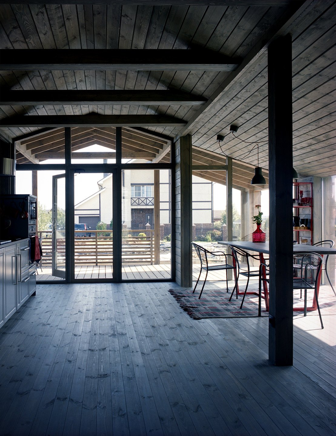 """With its timber rafters and expanses of glass, the house contrasts with its more conventional neighbors. To keep the focus on the views, Anna opted for minimal furnishings. The final design is the result of many imagined interiors, she explains: """"I dreamt about this house for some time—then I saw it in real life."""" In the dining area, a pair of IKEA Hektar pendants hangs over a table designed by Anna's employees as a gift. The chairs are from European home improvement store Obi; the rug is vintage."""