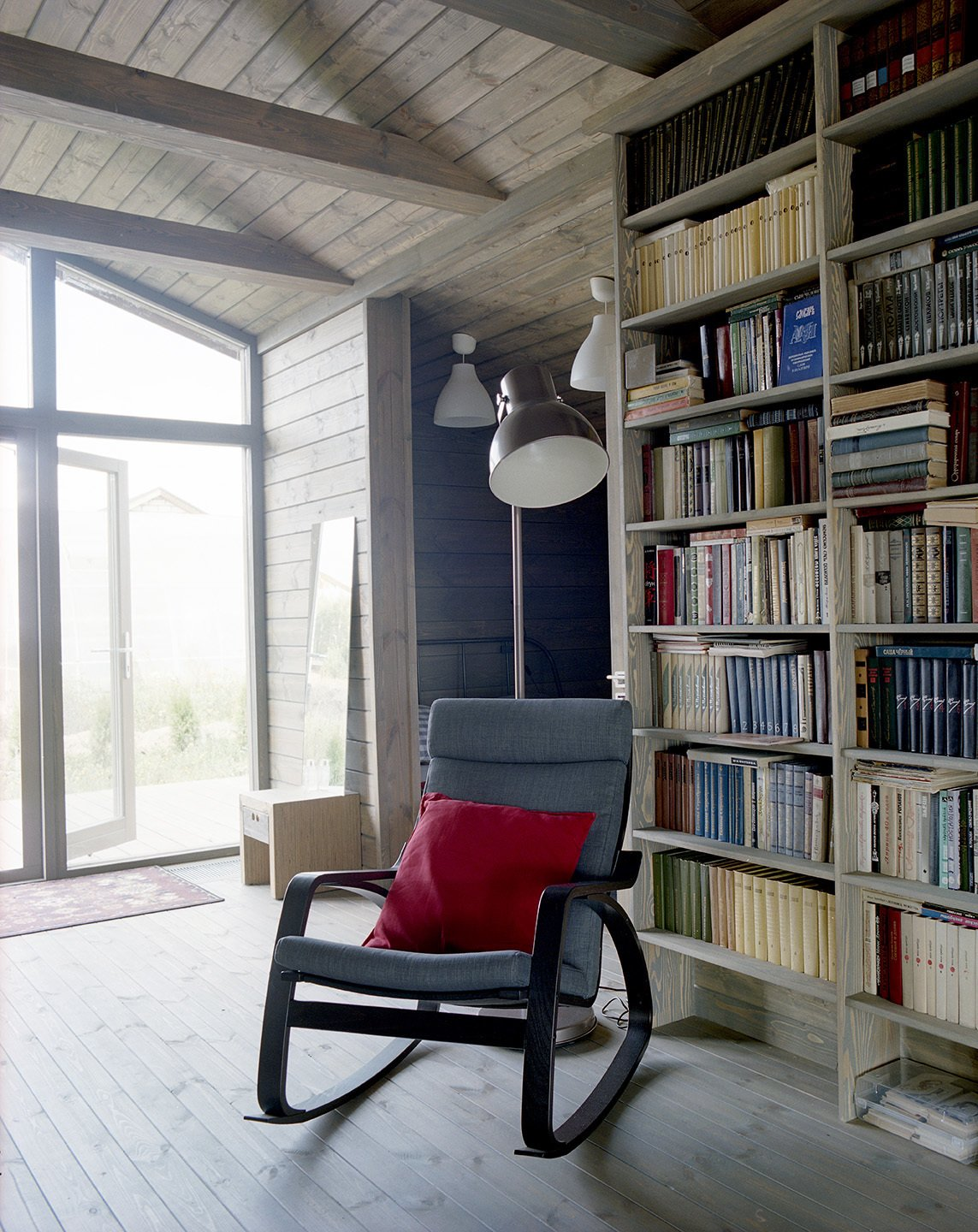 Near a Gent wood-burning stove by Thorma in the living area, an IKEA Poäng chair and ottoman provide a cozy spot for reading. Thanks to the passive design strategies utilized by Ovchinnikov, the house stays warm through the winter with only minimal heating required.  Photo 5 of 8 in Seeing Double
