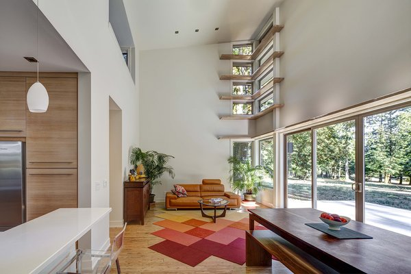 """Four rows of narrow """"light shelves,"""" a stylistic signature of Stillwater Dwellings, wrap around a corner wall in the double-height living room. A modular carpet by FLOR covers eucalyptus planks from Cali Bamboo. The leather Violino sofa was purchased at an overstock warehouse."""