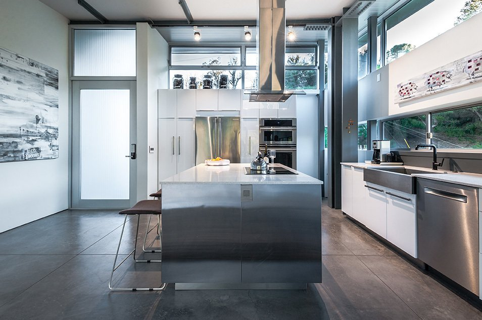 The house is laid out on three levels, with the main entrance leading to the top-floor kitchen, which features concrete floors, quartz counters, a refrigerator and wall oven by Electrolux, and a stainless-steel apron-front sink from Kraus. Tagged: Kitchen, Refrigerator, Wall Oven, Range, Range Hood, Cooktops, Microwave, Dishwasher, Quartzite Counter, Concrete Floor, Accent Lighting, Undermount Sink, Ceiling Lighting, and Engineered Quartz Counter.  Photo 4 of 5 in From the Ashes