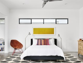 A third module, perpendicular to the main living areas, contains the master bedroom, which is furnished with a bed from Design Within Reach, a rug from Crate and Barrel, and a watercolor by Marfa artist Nick Terry. The saddle leather chair is by local furniture maker Garza Marfa.